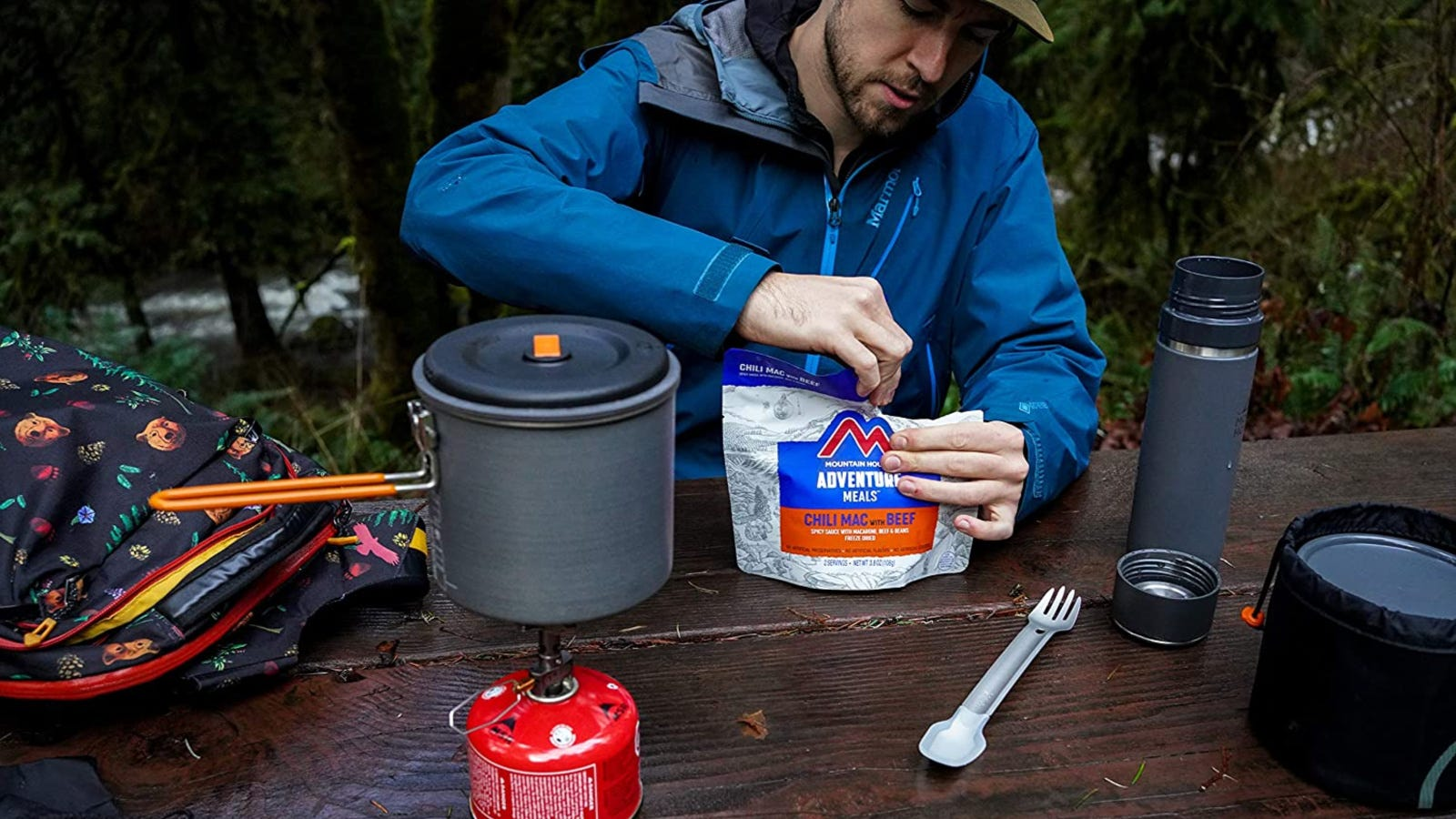 A hiker sitting down at a table opening up a mountain house meal while his water heats up in his cookware.