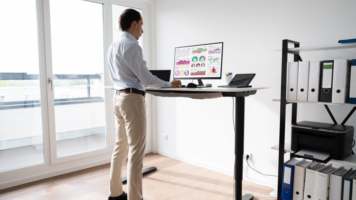 A man working on a computer at a standing desk in a home office.