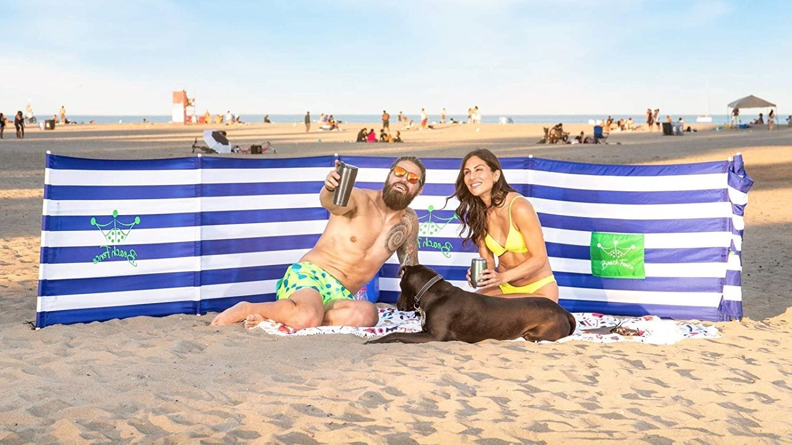 A man, woman, and brown Labrador dog sitting on the beach behind a blue-and-white striped Beach Fence.