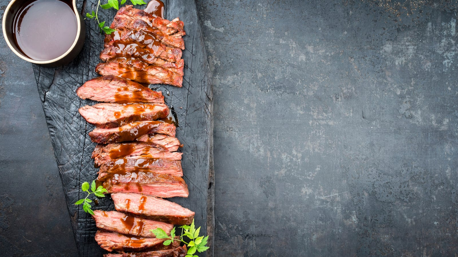 a sliced flank stead drizzled with demi-glace sauce over the the top with a side of demi-glace.