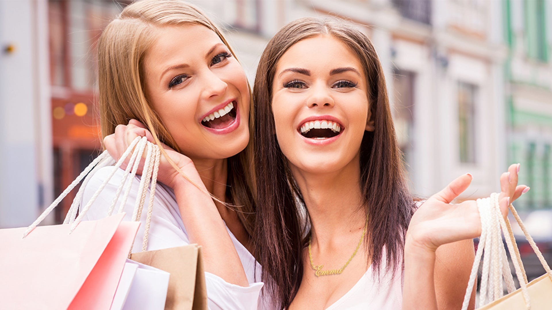 Two smiling girlfriends are out shopping and wearing name necklaces.