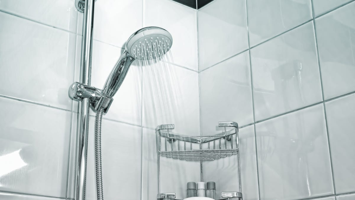 Water flows from a silver shower head over white shower tiles.