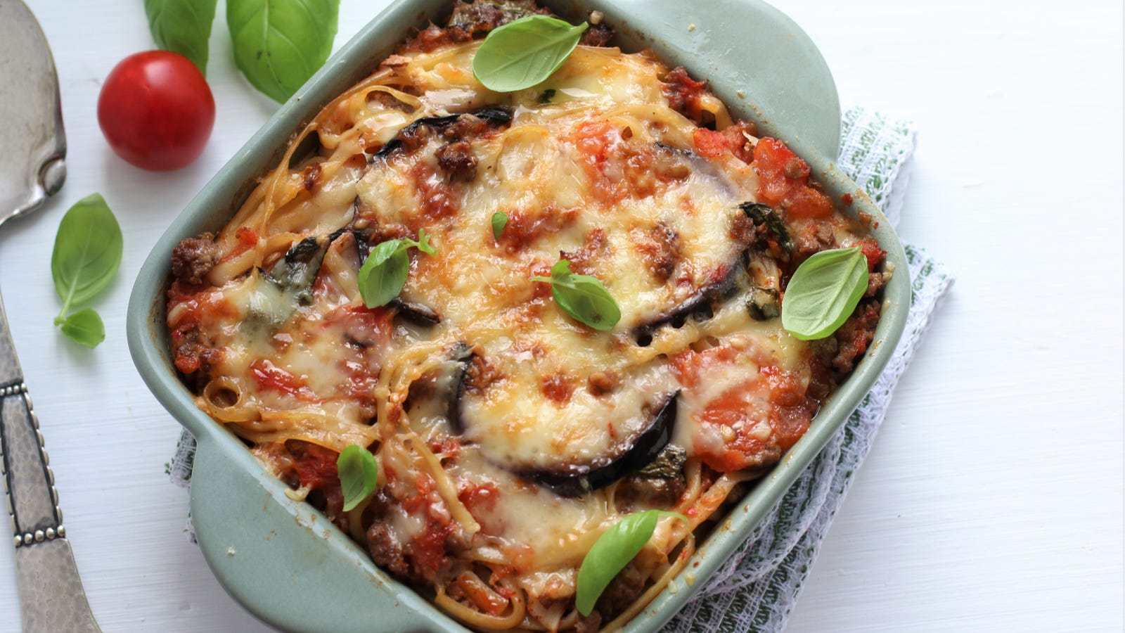 Baked eggplant over linguini with basil and cherry tomatoes on the side.