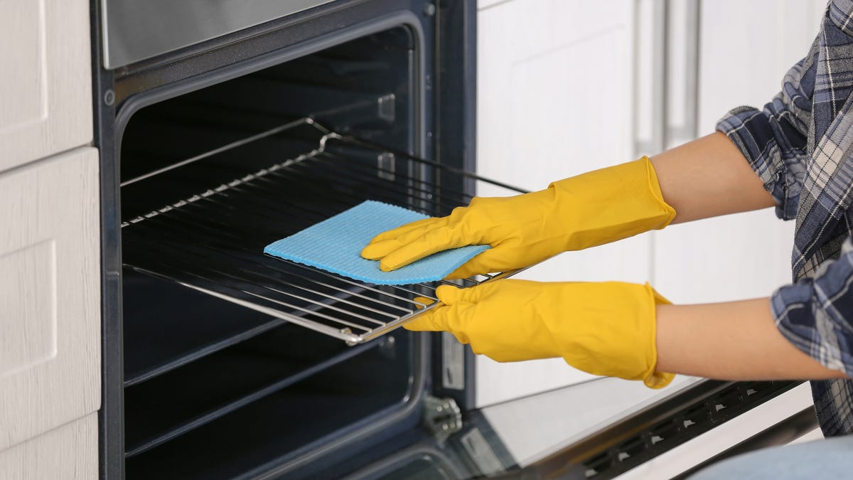 A person wearing yellow gloves cleans oven grates.
