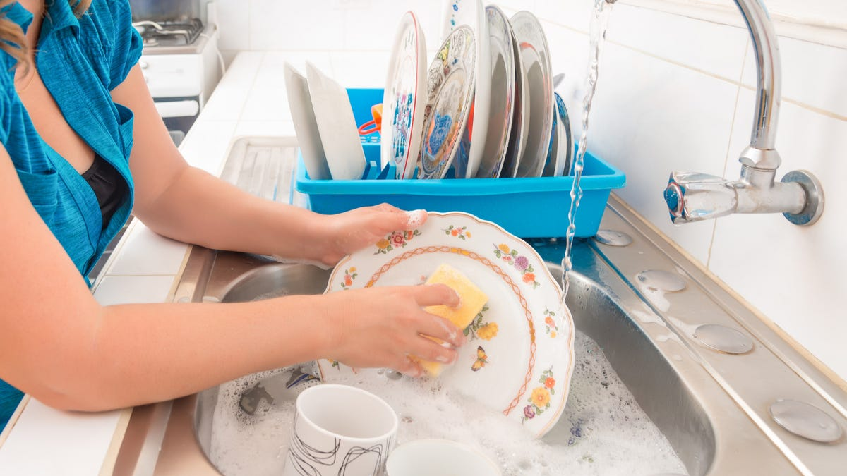 A person uses a sponge to wash a decorative plate in a sink with a running faucet.