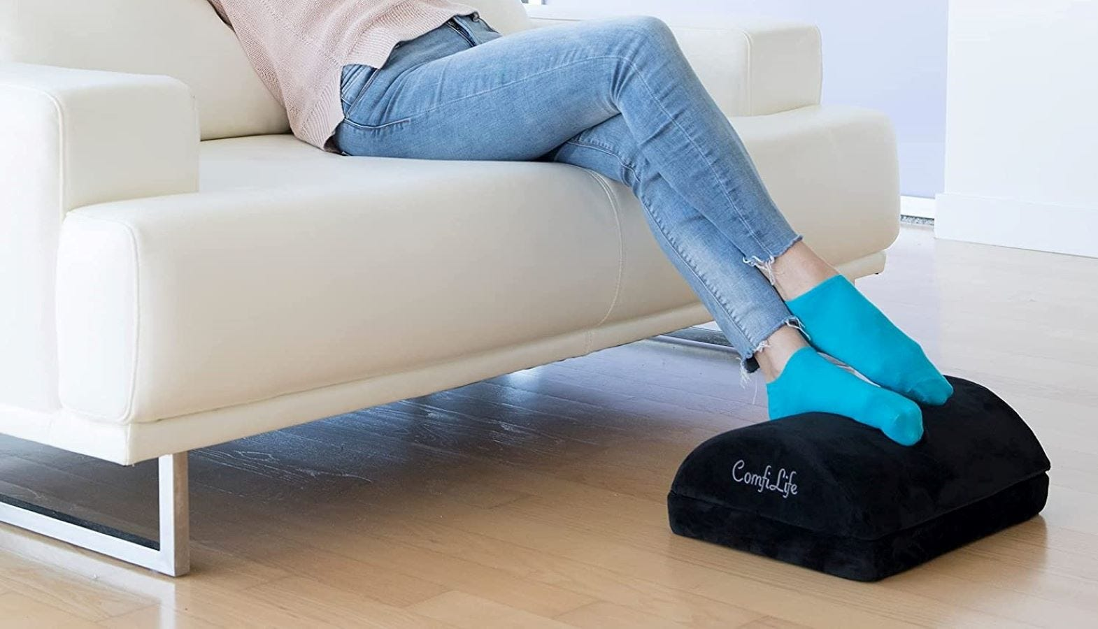 A woman sitting on a couch and resting her feet on the ComfiLife Foot Rest.