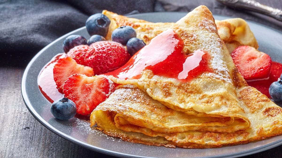 Crepes with fresh berries and sauce on a plate.