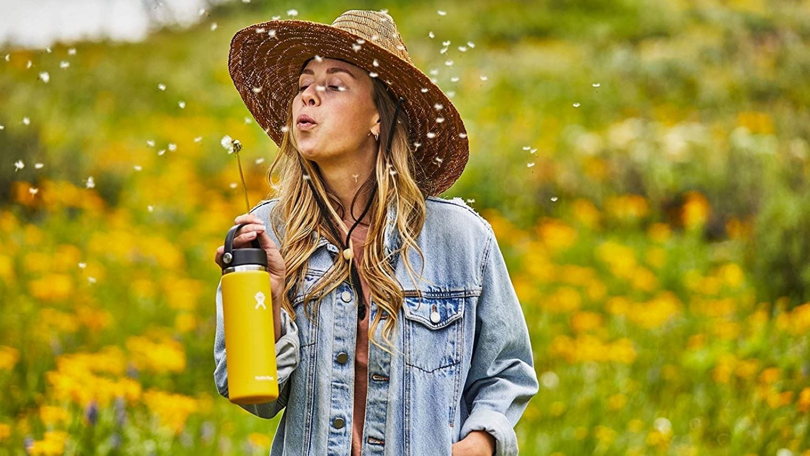 A woman blowing on a dandelion flower in a field while carrying a yellow Hydro Flask.