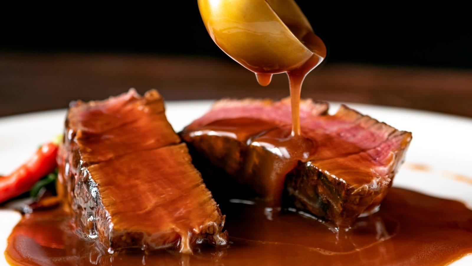 Pouring demi-glace over a sliced filet mignon steak.