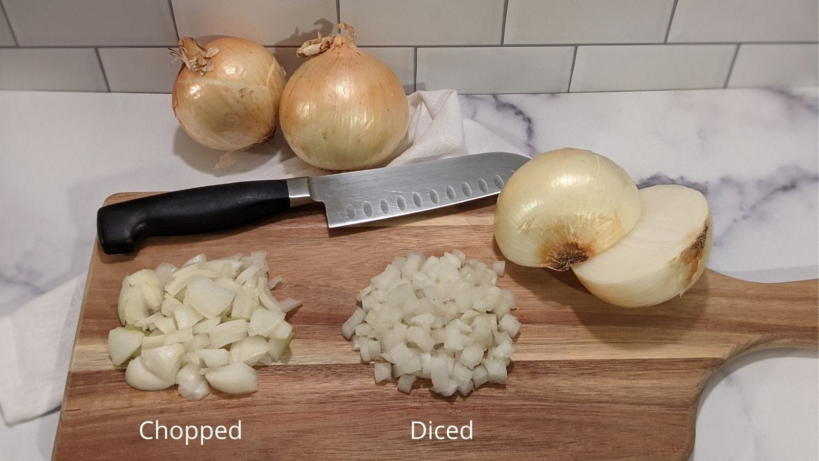 A cutting board with two small piles of onion displaying what chopped onion and diced onion looks like.