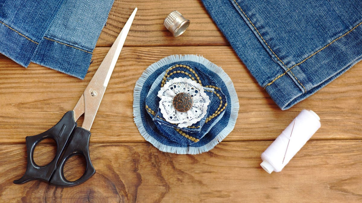 A pair of jeans, scissors, thread, a thimble, and a denim flower brooch on a table.