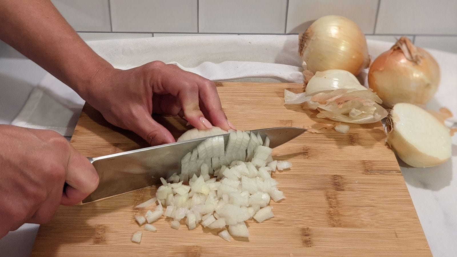 Dicing an onion in uniform peices with peels and onions in the background.