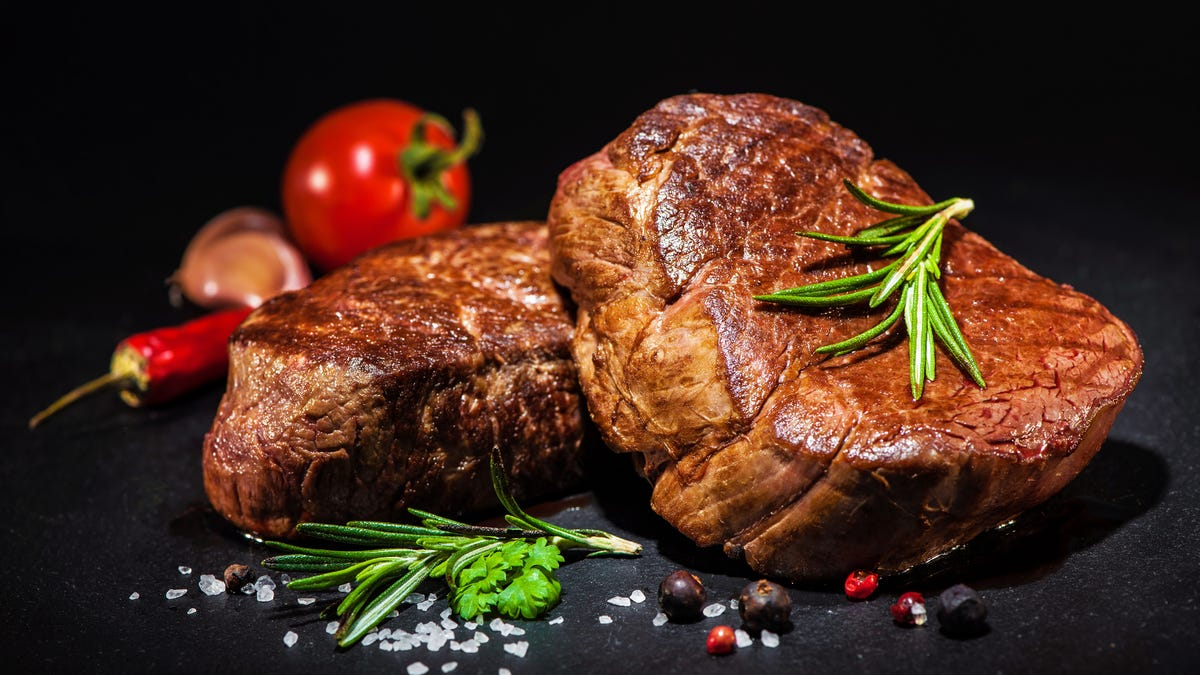 A steak is propped on top of another and surrounded by salt, tomato, and thyme.