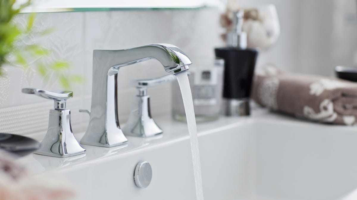 A silver sink faucet runs water into a basin.