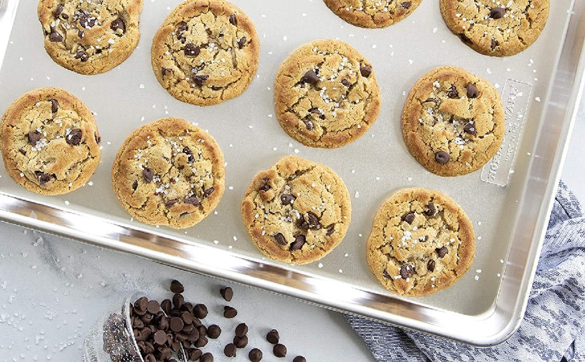 A close-up of chocolate chip cookies on an aluminum pan, surrounded by sea salt and chocolate chip cookies.