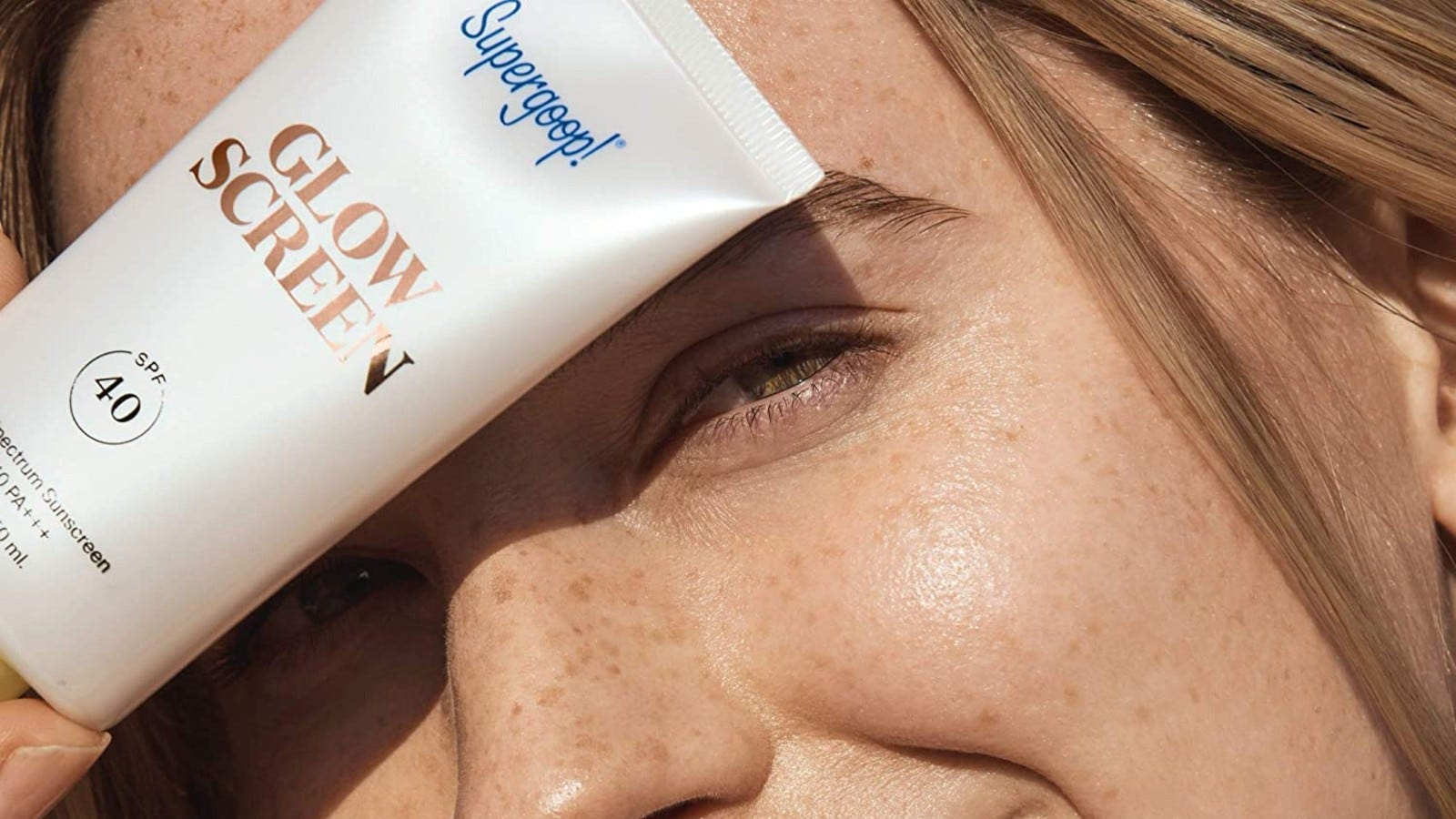 close up of girl's face holding supergoop glow screen