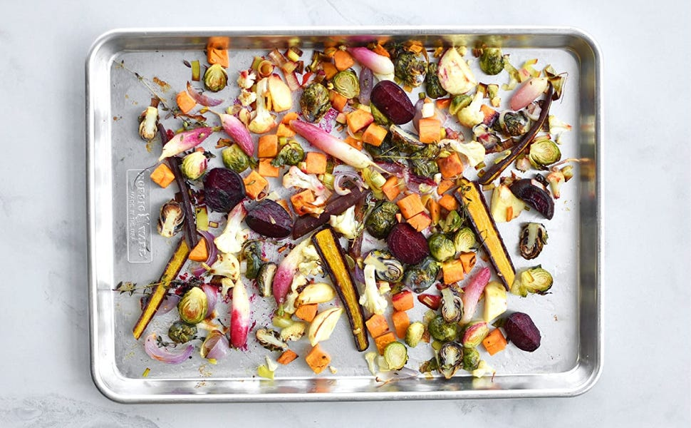 A top view of an aluminum pan filled with roasted vegetable on a marble counter.