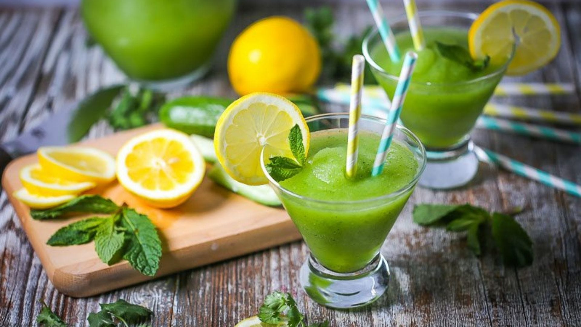 Frozen green cocktails next to lemons and mint