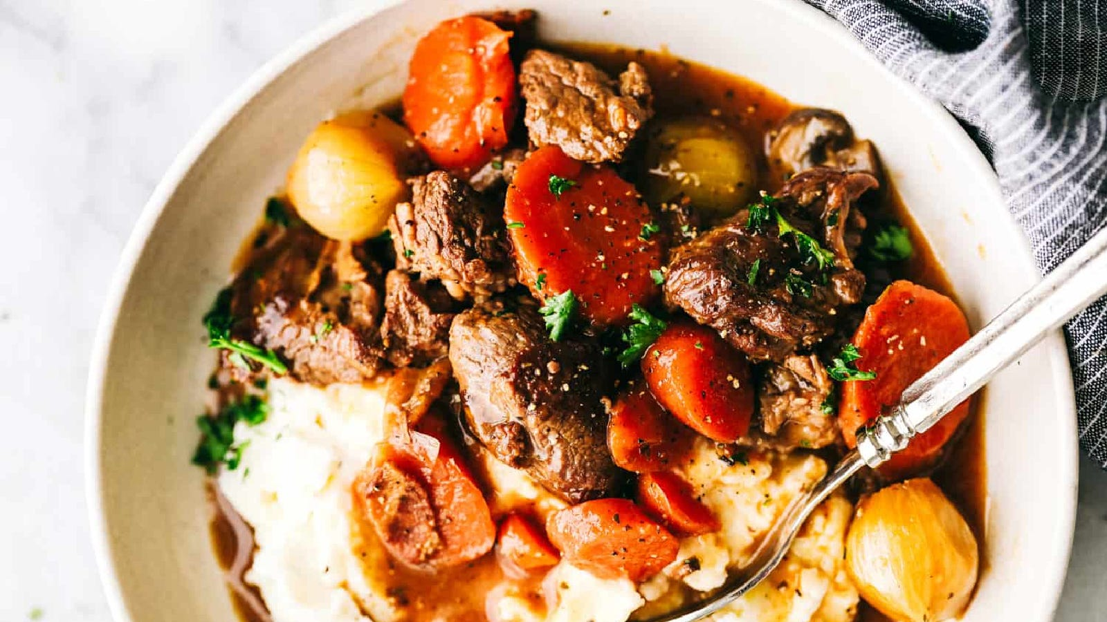 A bowl of hot beef bourguignon with a spoon