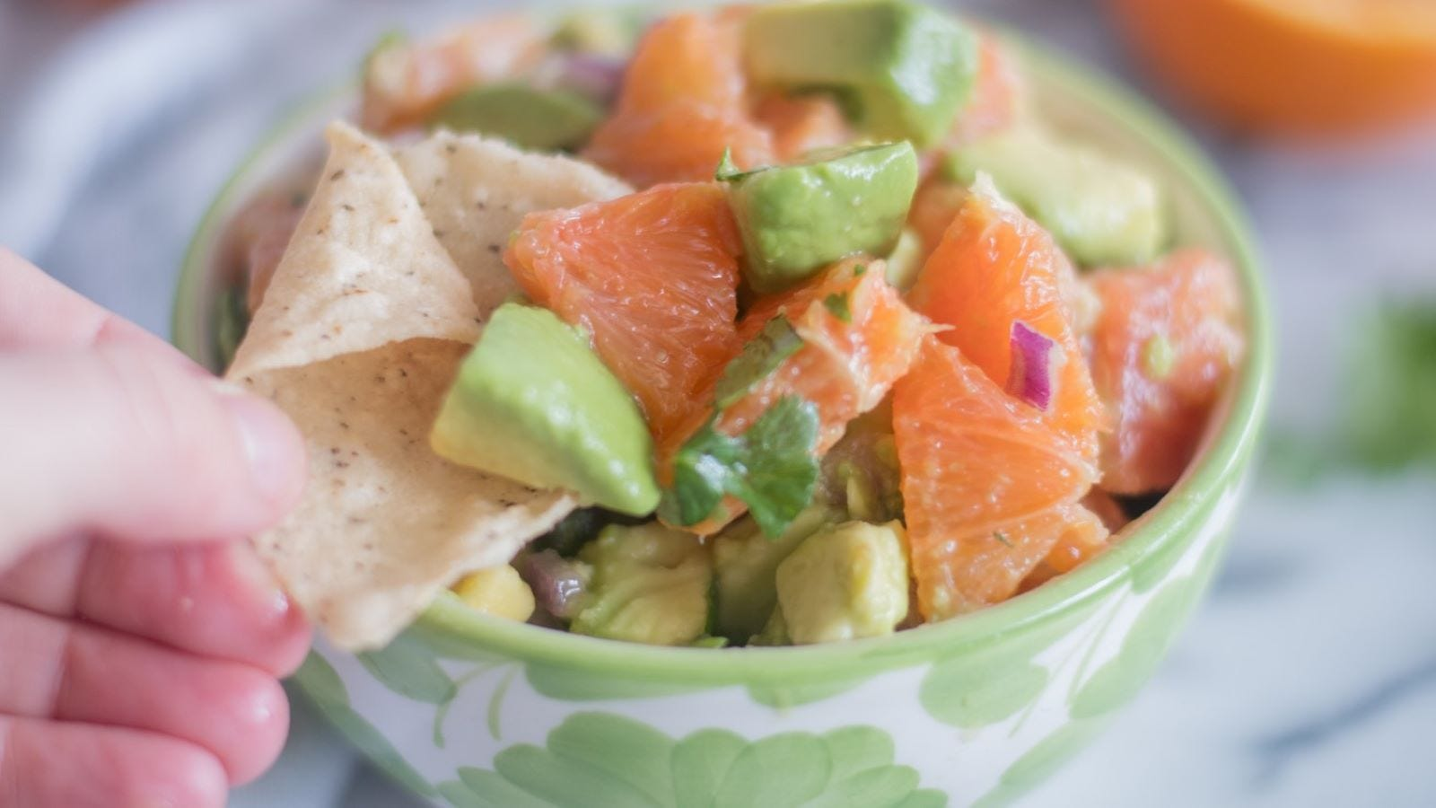 Someone dipping a chip in a bowl of orange and avocado salsa.