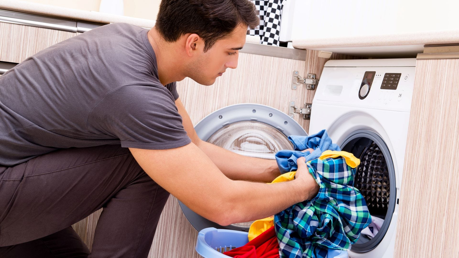 A man putting laundry in the dryer.