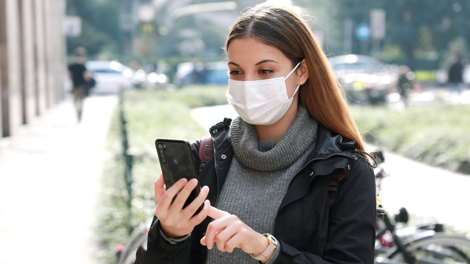 A young woman wearing a face mask on a college campus and looking at a map app on her phone.