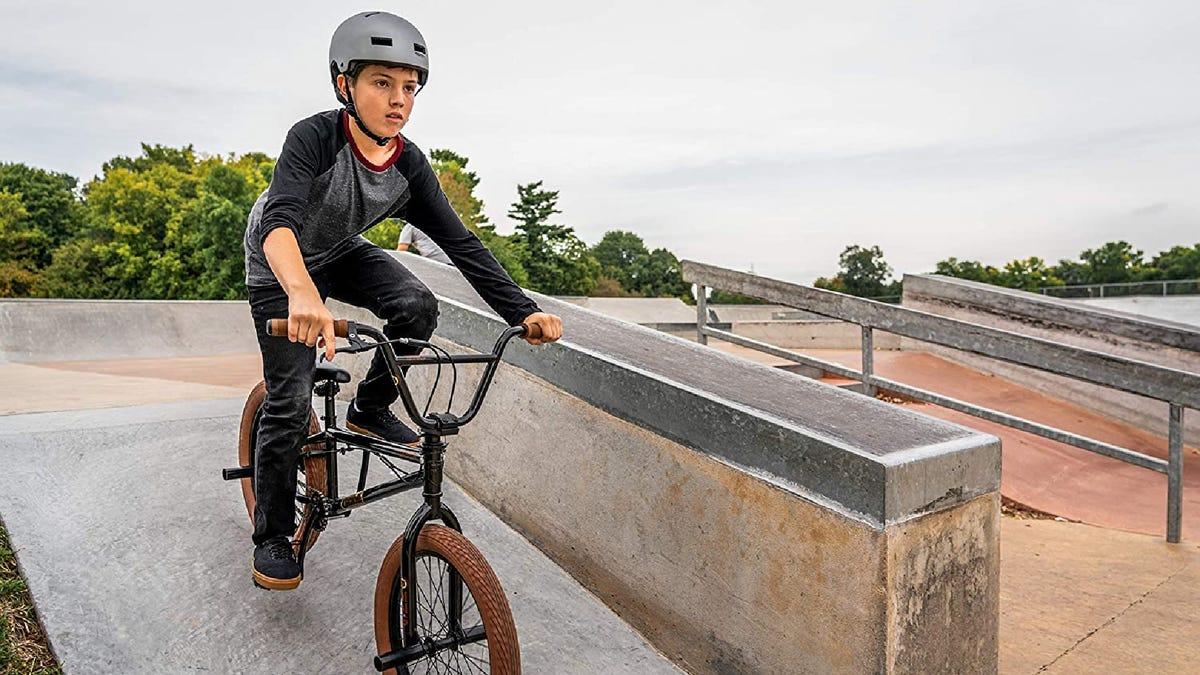 a boy with a helmet riding a BMX bike in a skate park