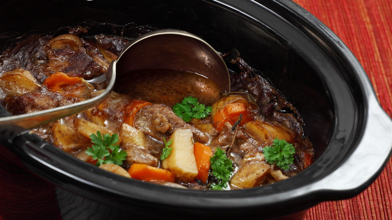 A ladle in a slow cooker full of beef stew.