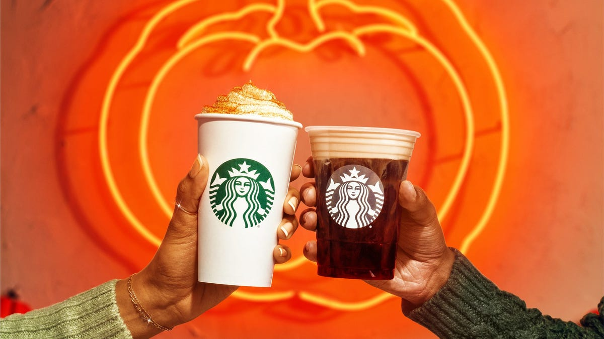 Two people hold up a pumpkin spice latte and an iced pumpkin spiced latte in front of a neon pumpkin sign.