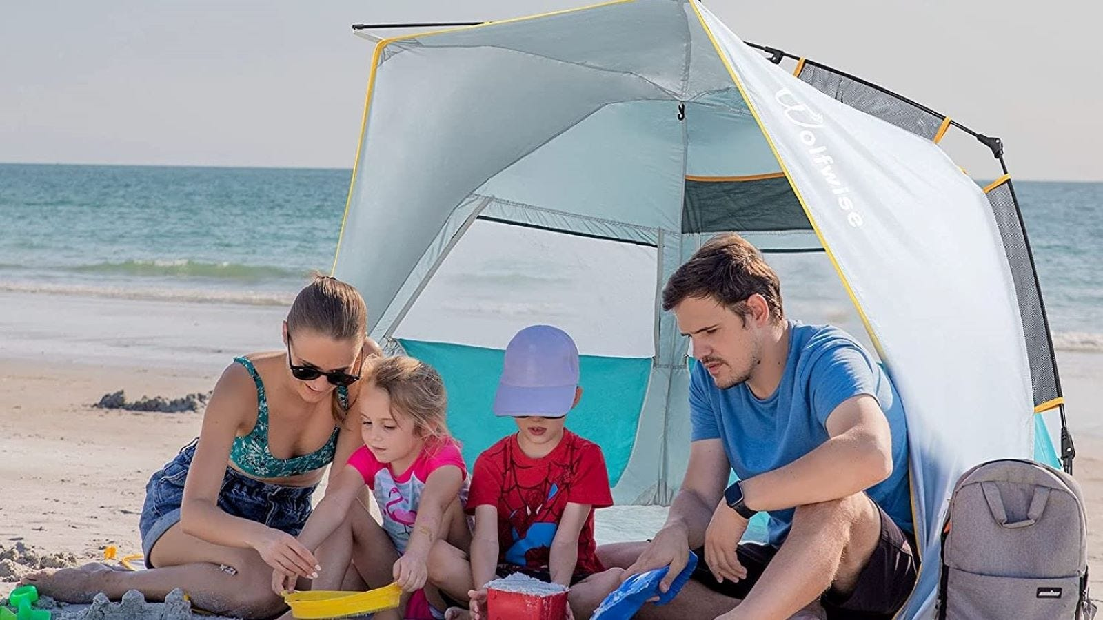A man, woman, and two children on the beach in a WolfWise Beach Tent.