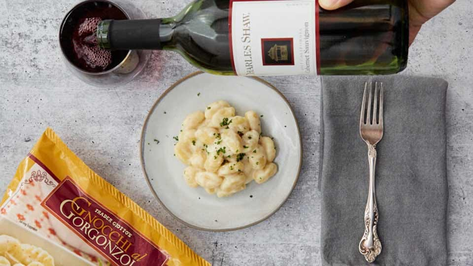 Someone pouring a glass of wine with plate of Trader Joe's gnocchi on the table.