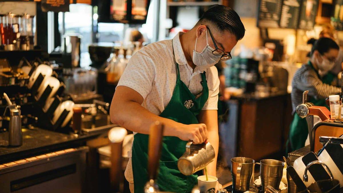 A barista prepares a coffee drink at Starbucks.