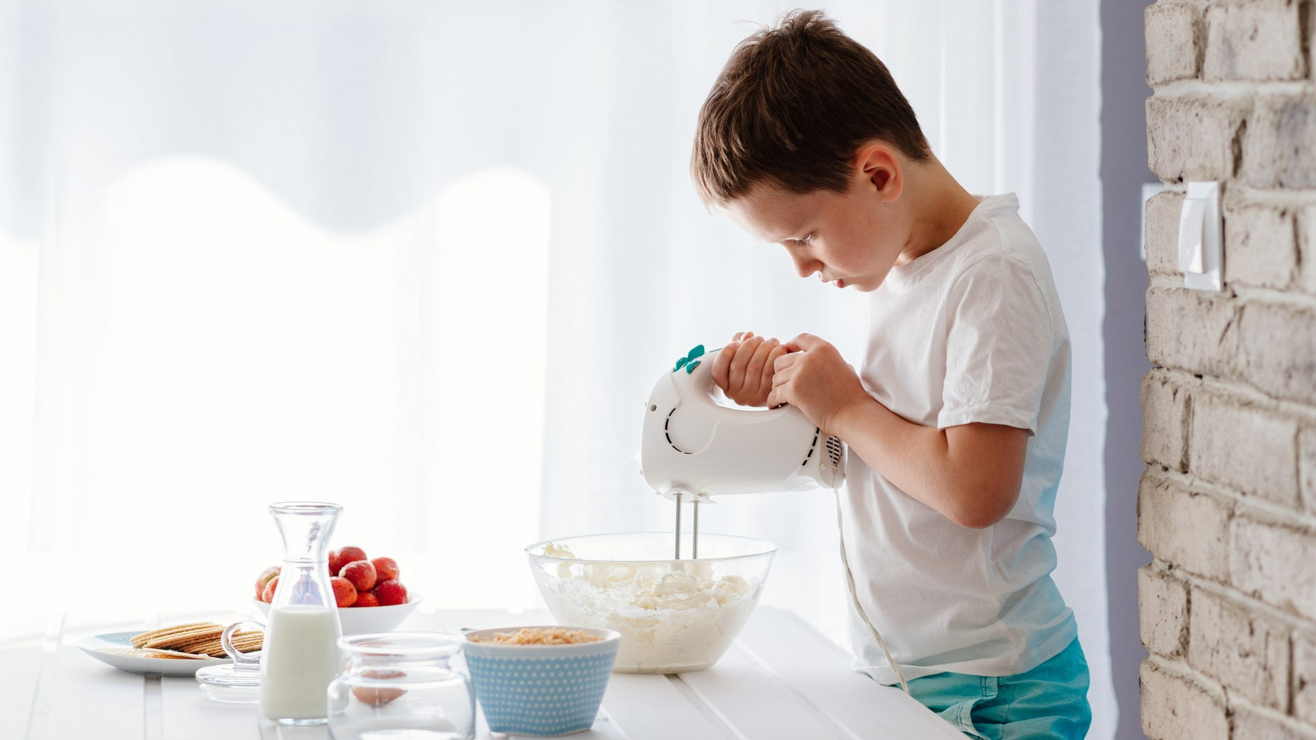 A boy uses a hand mixer to mix ingredients in a big glass bowl in the kitchen.