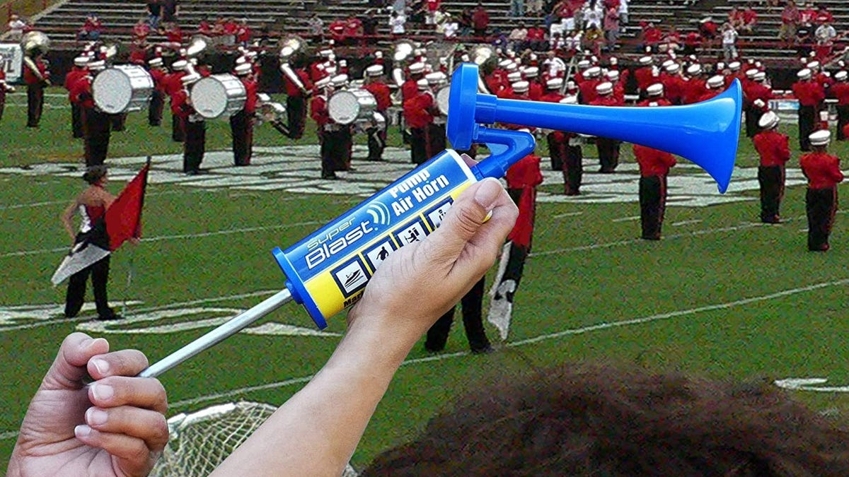 Someone using an air horn in the stands at a football game