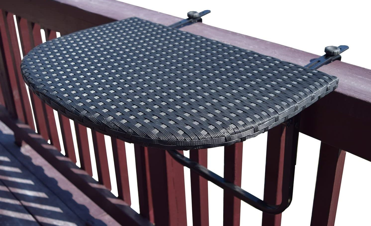 The Oakland Living Balcony Railing Wicker Table in black attached to a balcony rail.