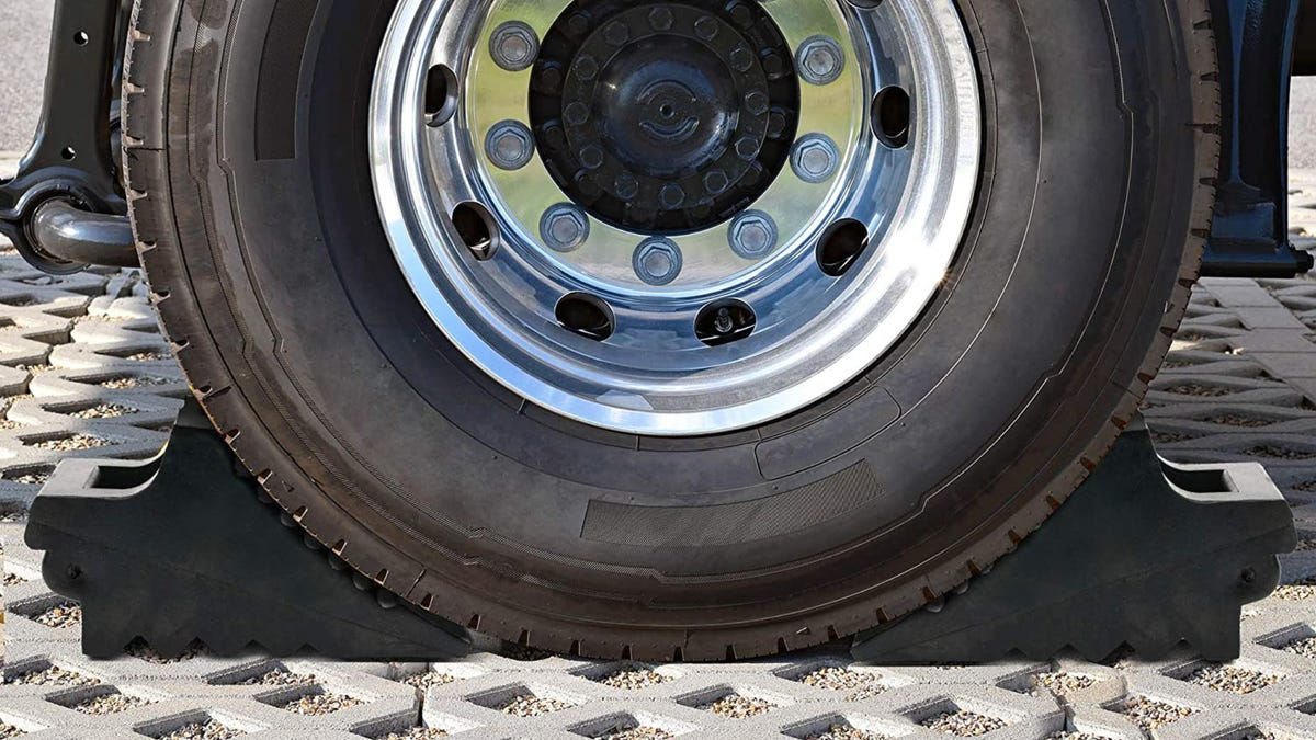A side view of a tire being held on both sides by a black chock.