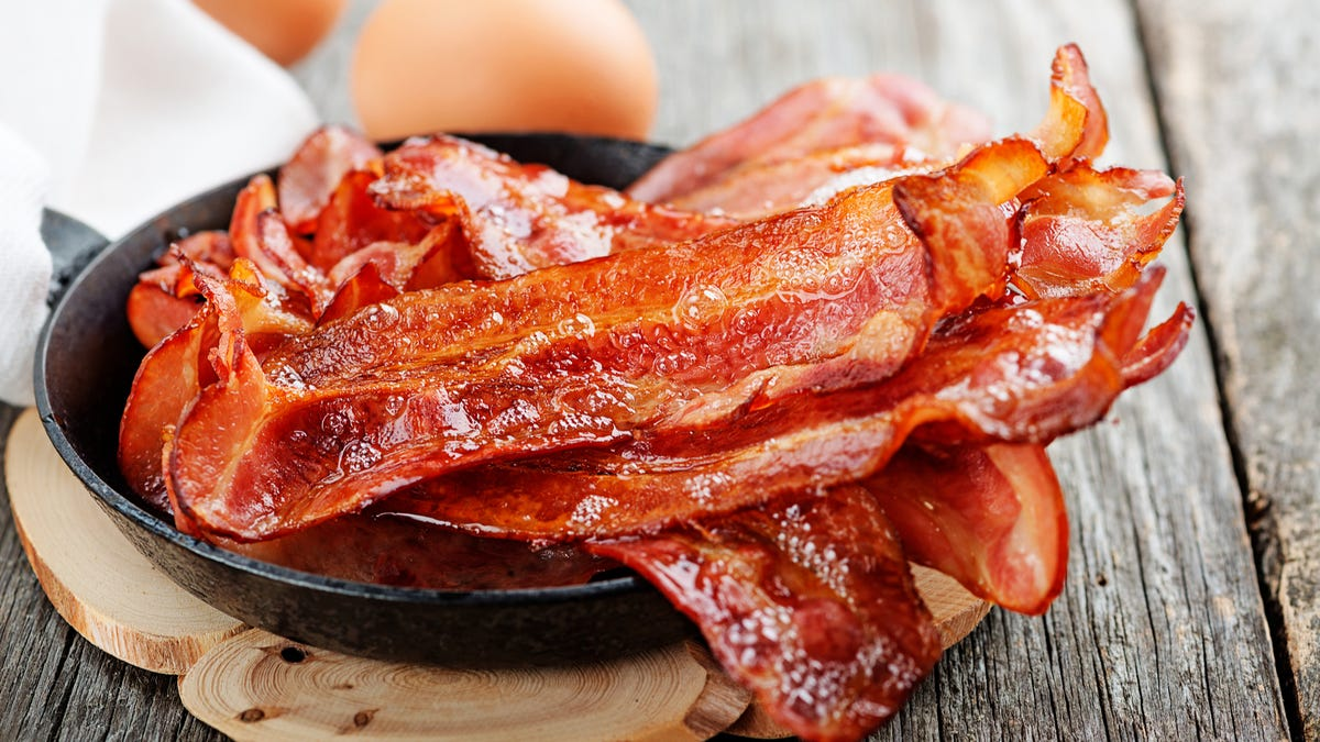 Cooked pieces of bacon sit in a cast iron skillet on top of a wooden cutting board.