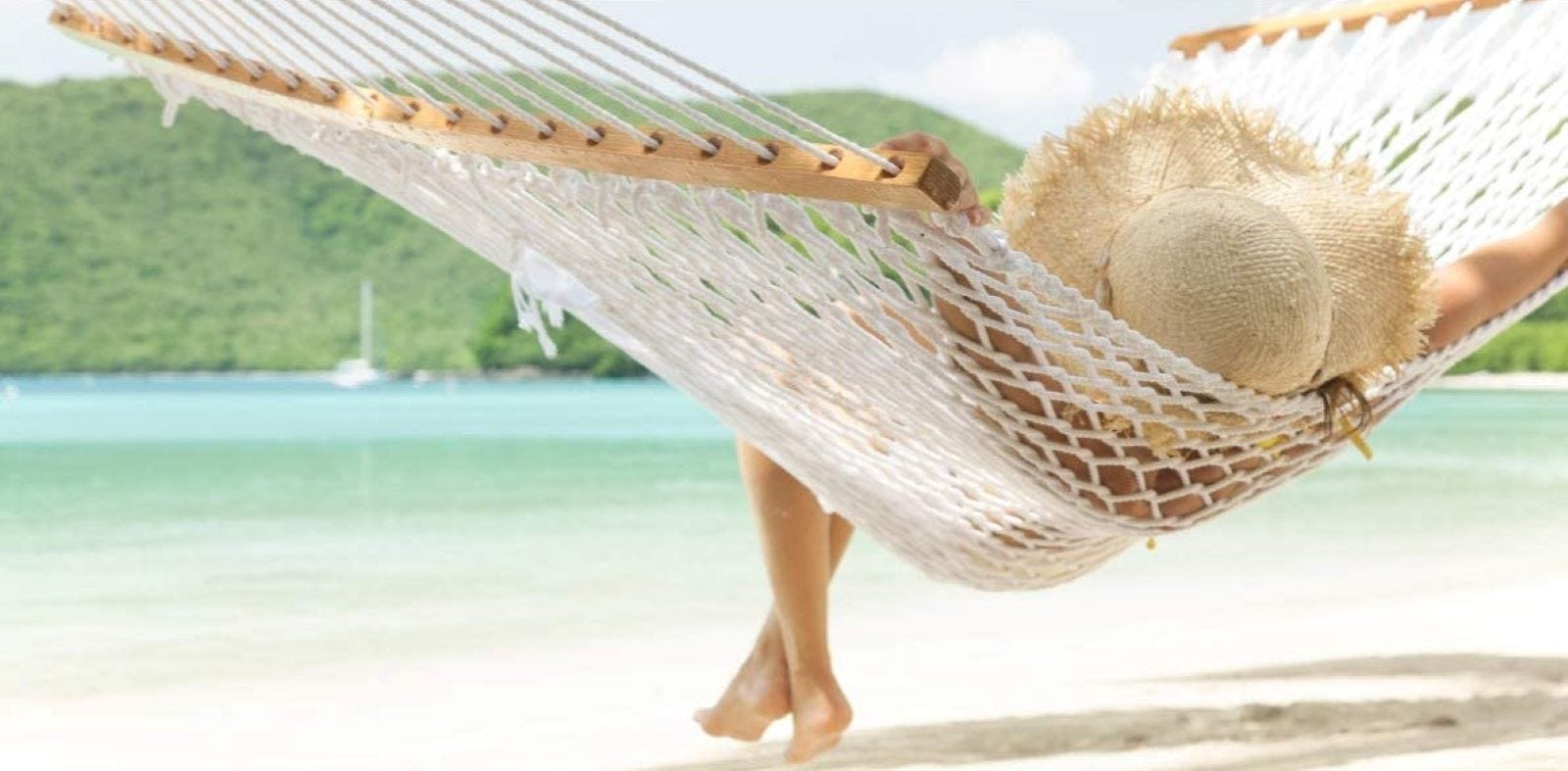 A woman resting in the Y-Stock hammock at the beach.