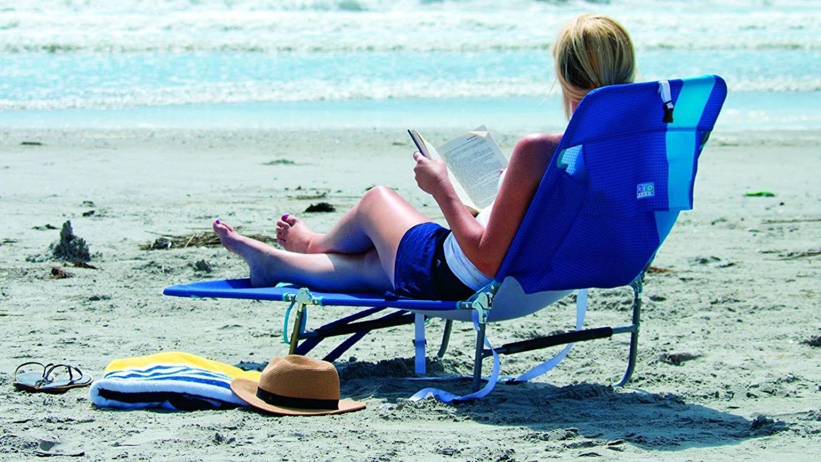 A woman reading at the beach on the blue stripe RIO Beach chair.