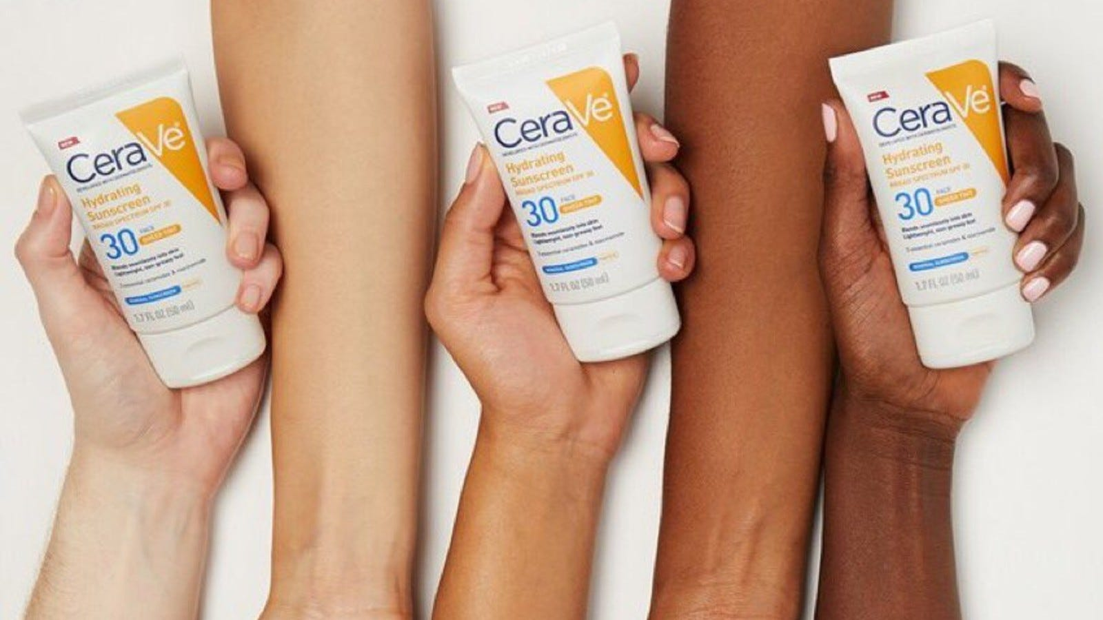 three hands in different skin tones holding Cerve sunscreen bottle
