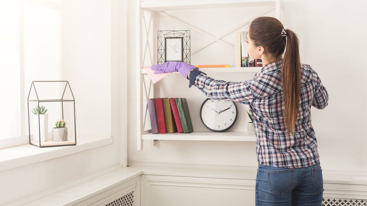 A woman uses a rag to dust shelves.