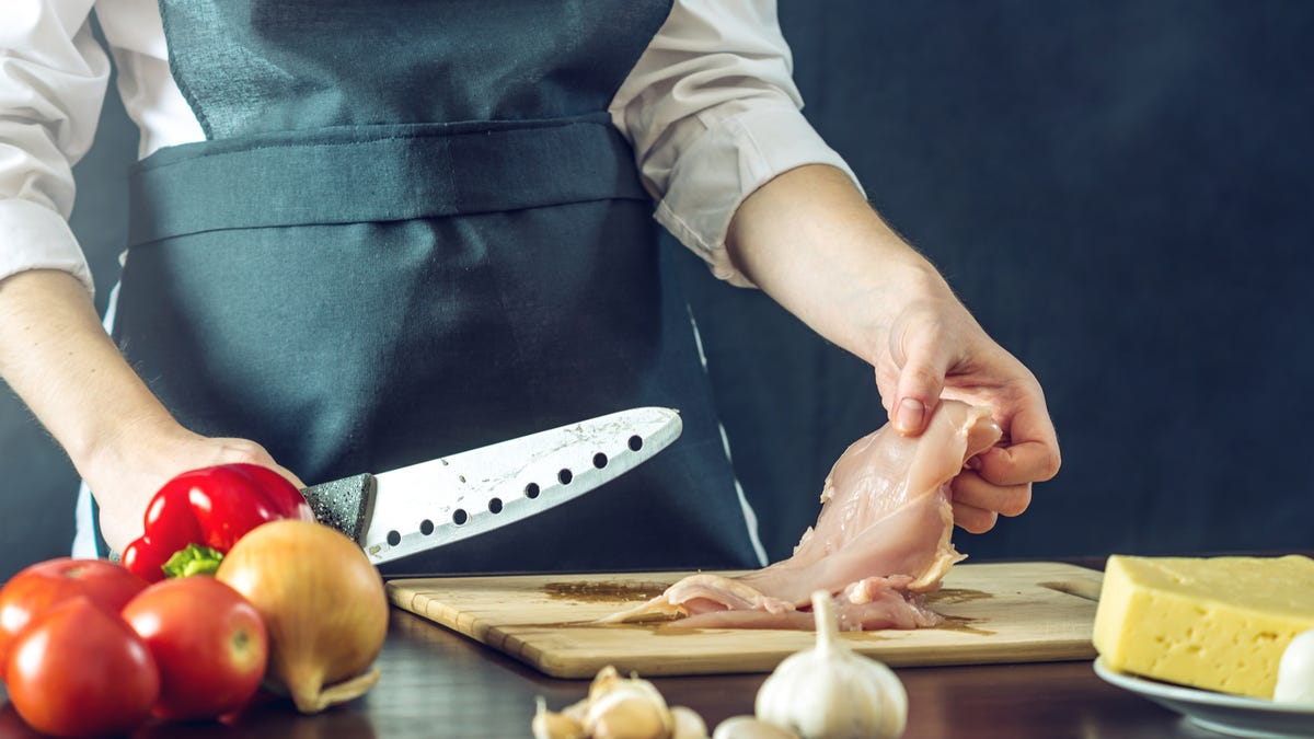 A person holds a knife in one hand and a piece of raw chicken in the other.