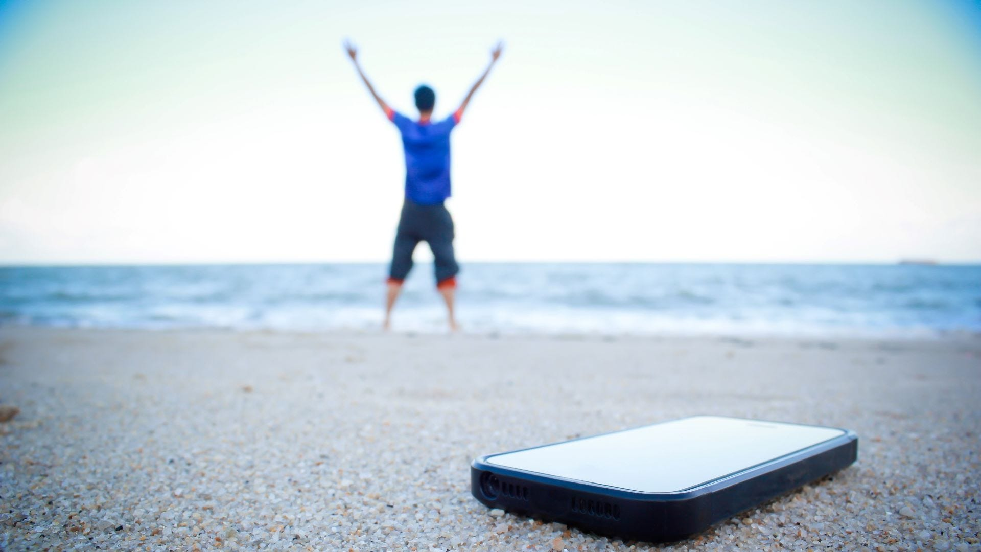 Man at the beach, his phone lying behind him in the sand.