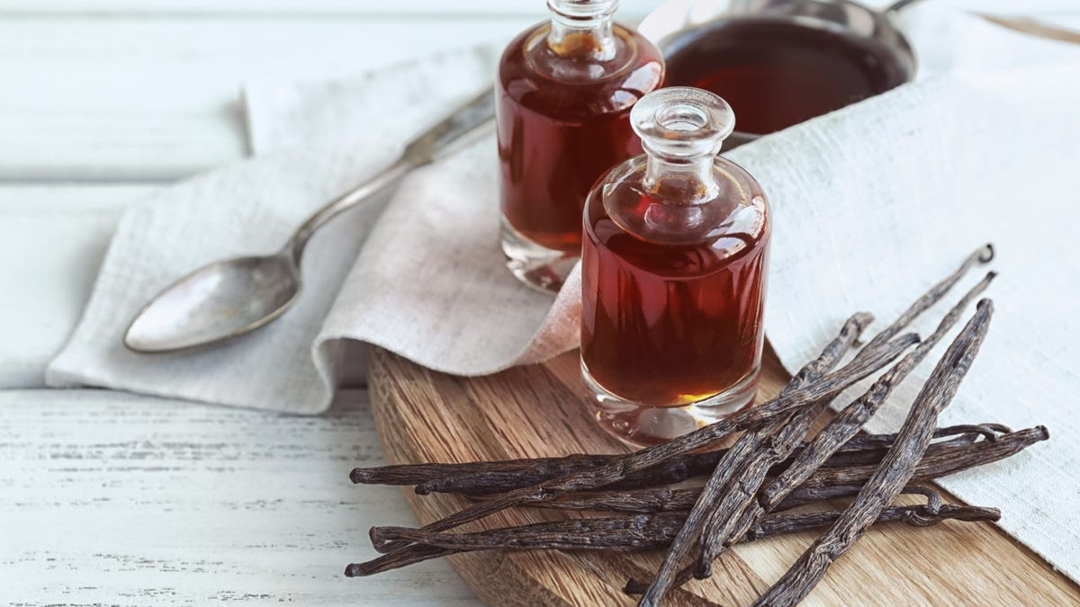 Two clear glass bottles of vanilla extract sit next to a stack of vanilla beans on top of a wooden cutting board.