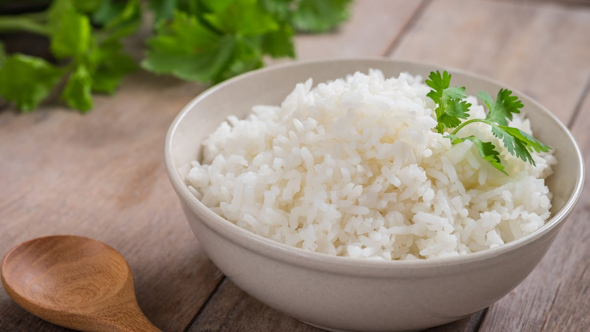 A bowl of white rice sits next to a wooden spoon.