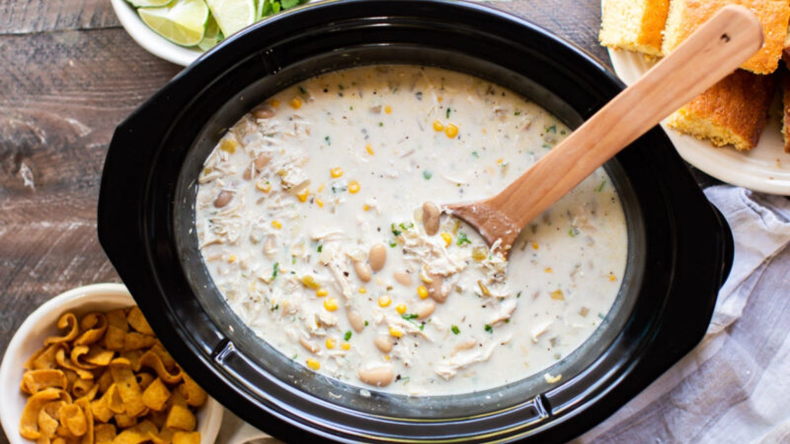 White chicken chili in a crock pot with fritos, lime and corn bread on the side.