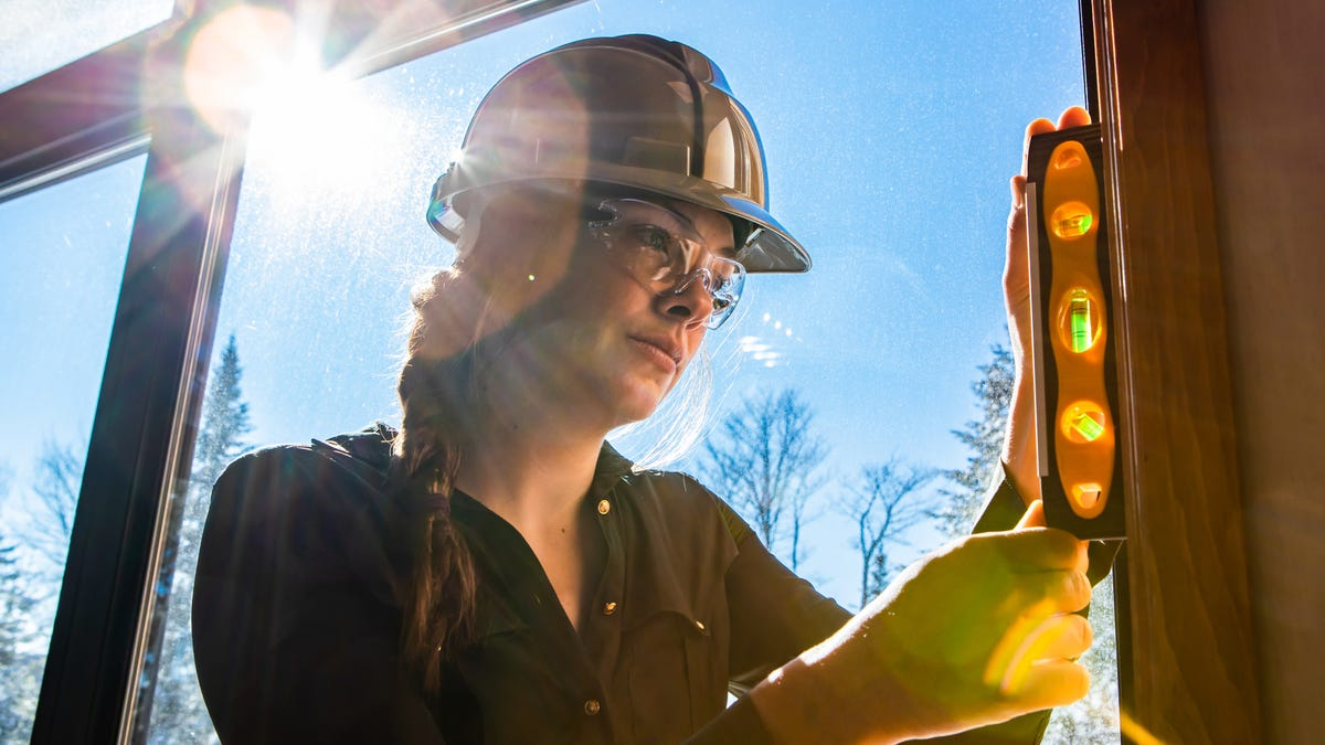 Close-up on worker using a level on vertical surface next to a window with sun in the sky view.