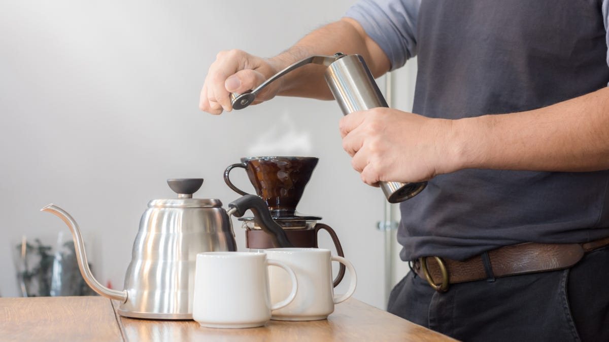 A Person manually grinding coffee beans for his pour over coffee.