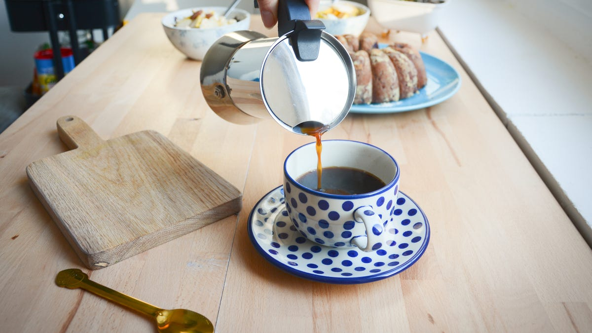 A person pours coffee into a blue and white polka dot cup.