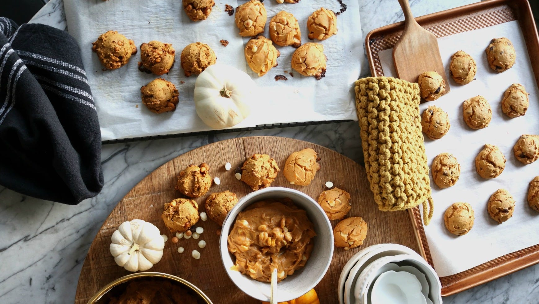 A counter with a baking sheet with cookies on it and a board with pumpkin and other ingredients
